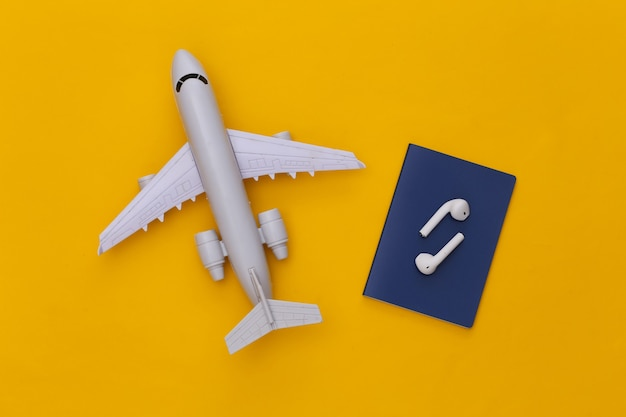 Passeport et écouteurs sans fil, avion sur fond jaune, concept de voyage.