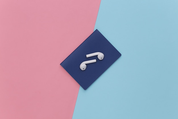 Passeport et écouteurs sans fil sur fond pastel bleu rose, concept de voyage.