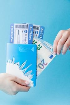 Passeport, euro et billet d'avion en main de femme sur bleu