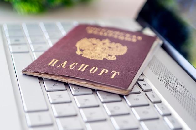 Passeport de la fédération de russie sur un clavier d'ordinateur portable gris. identification de l'utilisateur sur internet. interdiction d'accès à internet sans données de passeport. délivrance d'un passeport via internet