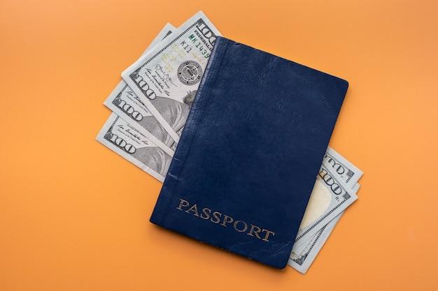 Passeport international bleu et billets en dollars américains sur fond rouge, vue de dessus.