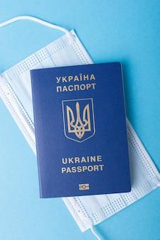 Passeport international du citoyen ukrainien sur un masque médical sur fond bleu