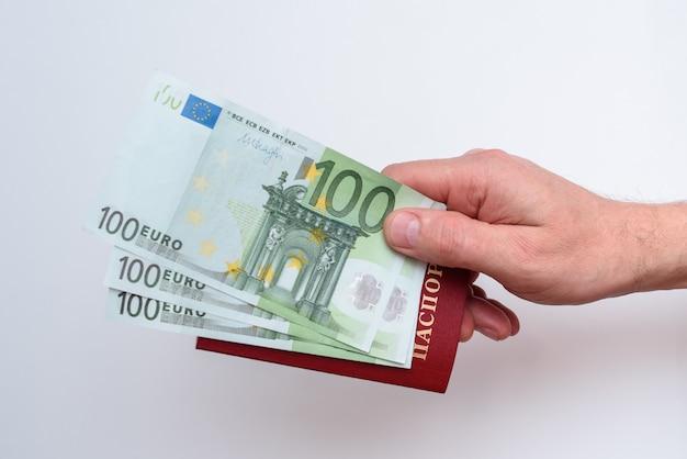 Passeport international russe avec euro dans la main de l'homme