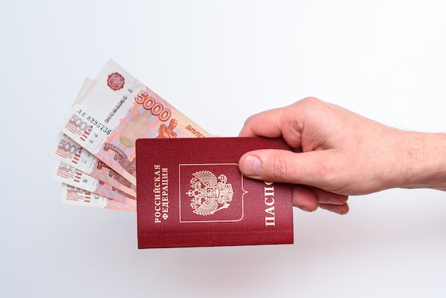 Passeport international russe avec des roubles dans la main de l'homme