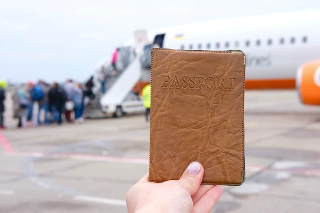 Passeport à la main sur le fond de l'avion avec des personnes à l'aéroport photo de haute qualité