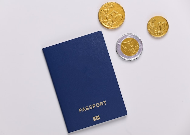 Passeport avec des pièces sur un blanc. concept de voyage ou d'émigration