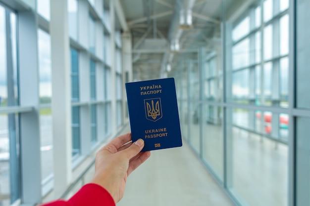 Passeport ukrainien en main à l'aéroport avant le départ. temps de voyage.