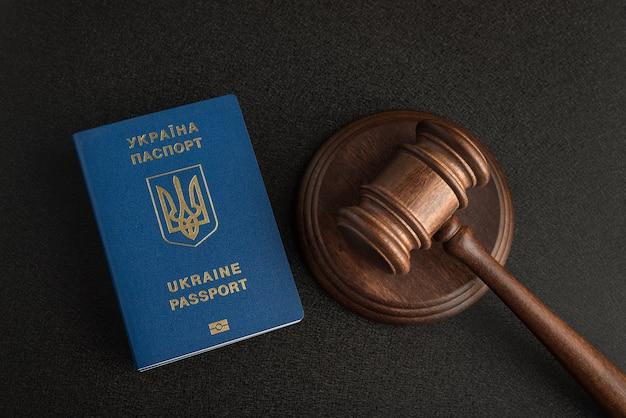 Passeport ukrainien et marteau de juge sur fond noir gris. l'immigration légale. obtenir la citoyenneté.
