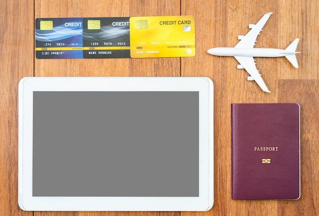 Passeport vue de dessus avec carte de crédit et tablette numérique maquette sur un bureau en bois