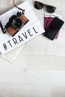 Passeports billets appareil photo lunettes de soleil téléphone intelligent et lightbox avec mot voyage