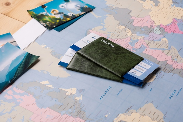 Passeports et billets placés sur une carte du monde papier avec des photos panoramiques