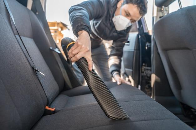Passer l'aspirateur à l'intérieur d'une voiture avec un respirateur sur le visage pendant une épidémie de coronavirus