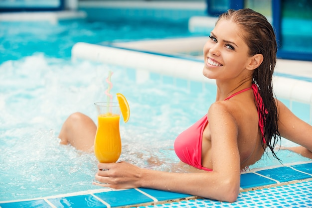 Passer du bon temps dans le jacuzzi. vue arrière de la jolie jeune femme en bikini se détendre dans le jacuzzi et souriant