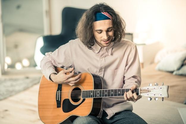 Passer du bon temps. souriant jeune artiste actif en chemise légère montrant sa maîtrise tout en jouant de la guitare