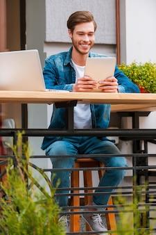 Passer du temps à l'air frais. gai jeune homme tenant une tablette numérique et souriant