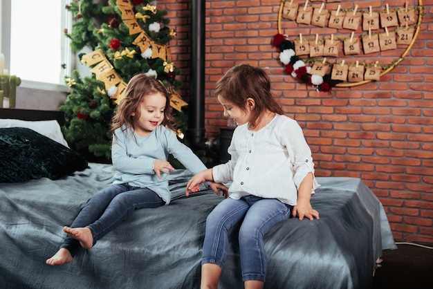 Passer du temps à jouer les uns avec les autres en attendant noël. les enfants sont assis sur le lit. conception du nouvel an.
