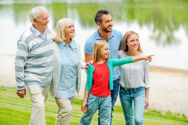 Passer du temps de qualité en famille. heureuse jeune famille marchant ensemble à l'extérieur pendant que la petite fille se dirige vers l'extérieur et sourit