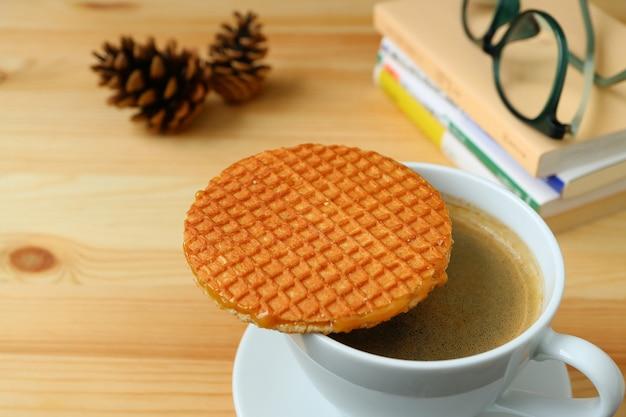 Passer du temps tranquille avec du stroopwafel et une tasse de café chaud servis sur une table en bois
