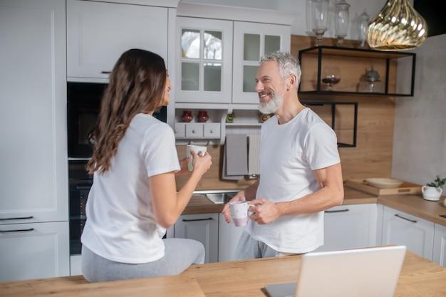 Passer la matinée ensemble. un couple ayant le café du matin dans leur cuisine