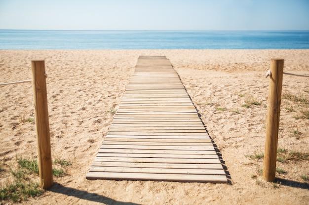 Passerelle en bois dans le sable sur la plage