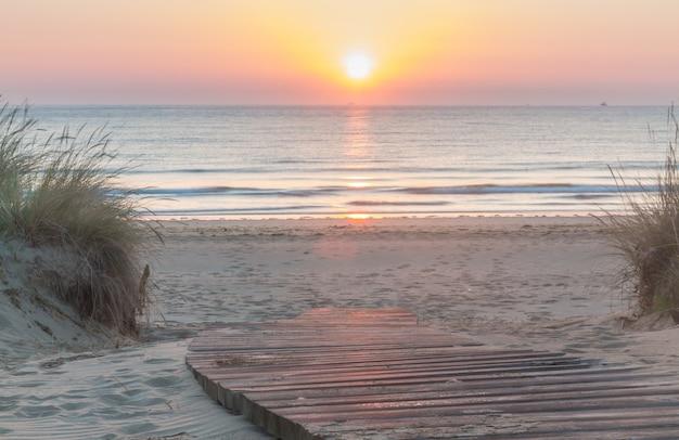 Passerelle en bois entrant dans la plage au lever du soleil