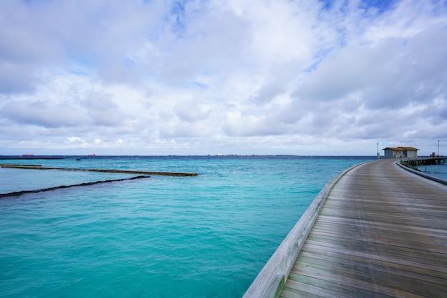 Passerelle en bois menant aux villas traversant l'océan turquoise dans une belle journée nuageuse sur l'île tropicale des maldives