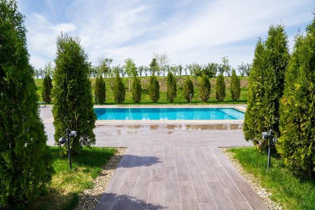 Une passerelle bordée de tuiles à la piscine entre les arbres. repos à la campagne. spa ou country club