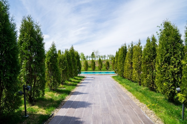 Une passerelle bordée de tuiles à la piscine entre les arbres