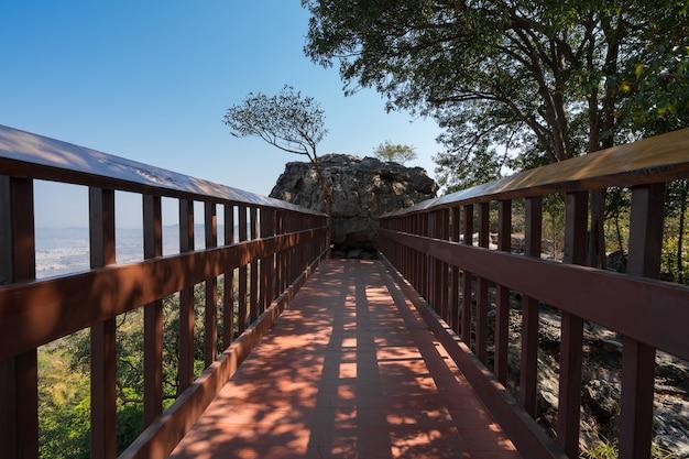 Passerelle piétonne de pont en bois vers un gros rocher avec une petite grotte sur la colline de la forêt avec un ciel bleu, pont vers un gros rocher à l'attraction de voyage du point de vue de pha muen à khon kaen, thaïlande