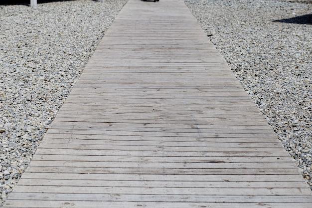 Passerelle vers la plage faite de planches de bois sur fond de galets