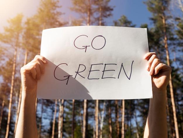 Passez au vert des mots écrits sur une affiche en papier dans des mains masculines dans la forêt.