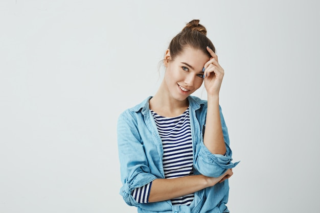 Passez la vie du bon côté. plan intérieur d'une jolie jeune étudiante caucasienne avec une coiffure chignon, tenant la main sur le front tout en inclinant la tête et souriant, étant timide.