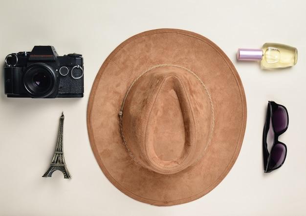 Passion pour les voyages, concept wanderlust. voyage en france, paris. chapeau en feutre, appareil photo argentique, lunettes de soleil, flacon de parfum, statue souvenir de la disposition de la tour eiffel sur un fond de papier pastel. mise à plat.