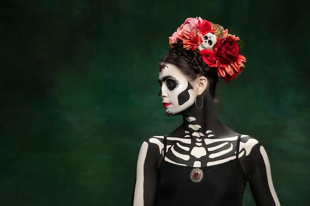 Passionné. jeune fille comme la mort de santa muerte saint ou le crâne de sucre avec un maquillage brillant. portrait isolé sur fond de studio vert foncé avec fond. célébrer halloween ou le jour des morts.