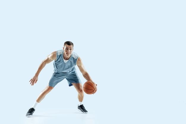 Passionné pour. jeune joueur de basket-ball caucasien de l'équipe en action, mouvement en saut isolé sur fond bleu. concept de sport, mouvement, énergie et mode de vie sain et dynamique. entraînement, pratique.