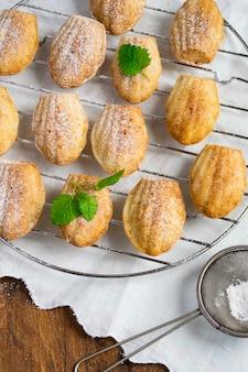 Passoire à biscuits madeleines fraîchement cuit avec du sucre en poudre