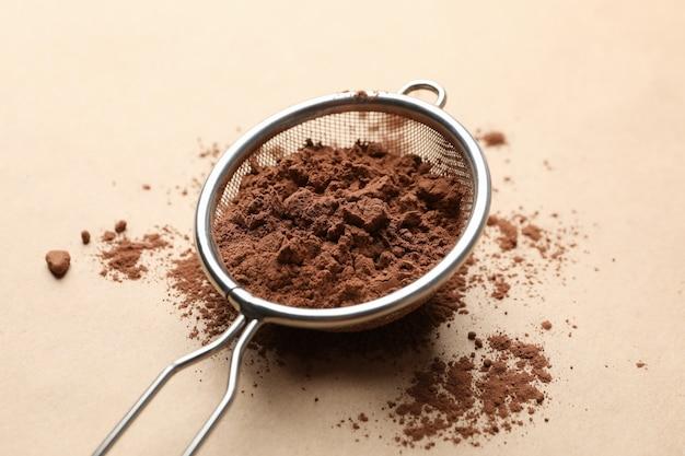 Passoire avec poudre de cacao sur carton, gros plan