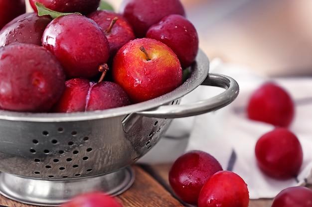 Passoire avec prunes juteuses mûres sur table, gros plan