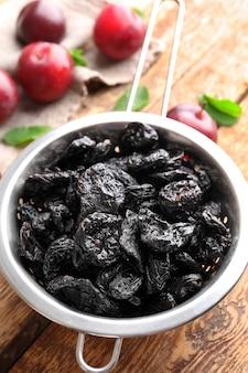 Passoire avec de savoureuses prunes séchées sur table