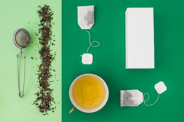 Passoire à thé, sachet de thé et boîtes blanches sur fond vert