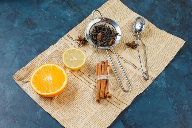 Passoires à thé avec un citron, une orange, un journal et de la cannelle