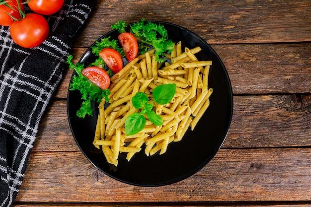 Pasta penne closeup avec la célèbre sauce italienne au pesto