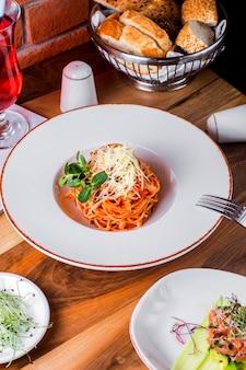Pastbolognese avec fromage verre de compote sel poivre et pain sur table