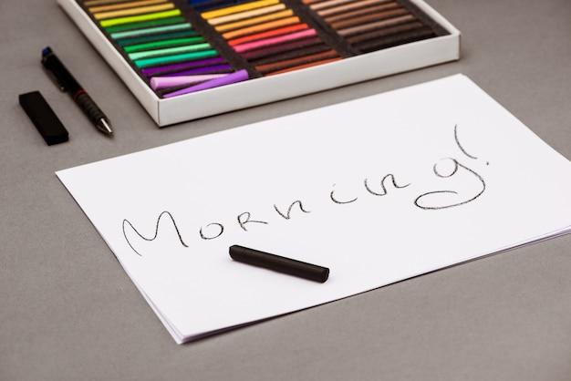 Pastel coloré, stylo, papier avec mot matin sur tableau gris