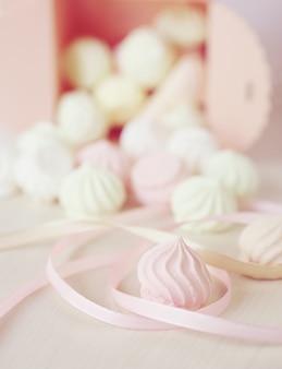Pastel fond romantique avec petites meringues dans une boîte