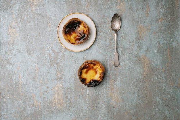 Pastel de nata. dessert traditionnel portugais, tarte aux œufs sur l'assiette et sur fond rustique. vue de dessus