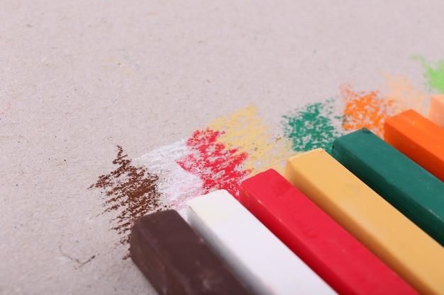 Pastels de craie colorés sur fond de papier de couleur