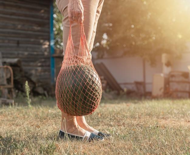 Pastèque dans un sac fourre-tout à cordes écologiques dans des mains de femmes le portant à l'extérieur
