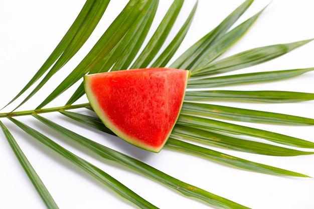 Pastèque sur des feuilles de palmiers tropicaux sur une surface blanche