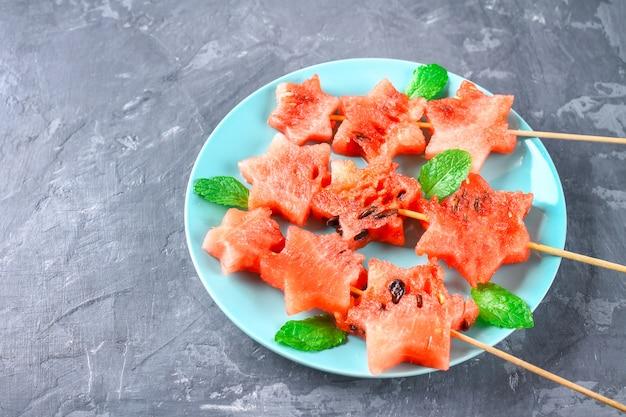 Pastèque en forme d'étoiles sur des brochettes avec des feuilles de menthe se trouve sur une assiette.